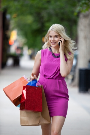 shopaholics: Portrait of attractive woman using mobile phone in city Stock Photo