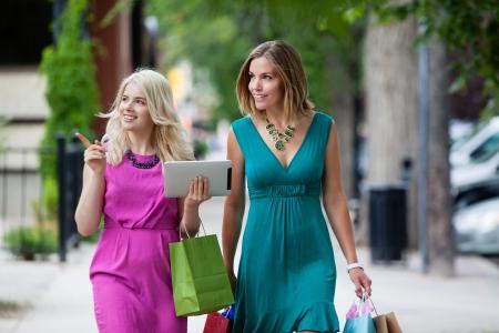 chicas de compras: Compras Mujeres con Tablet Digital en la calle Foto de archivo