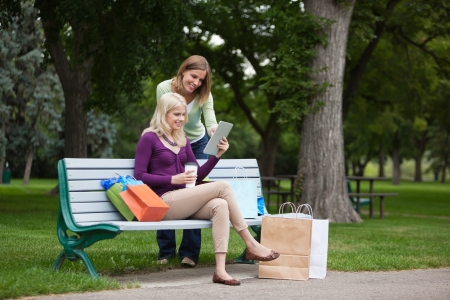 sitting on a bench: Beautiful young female friends with shopping bags using tablet PC on park bench