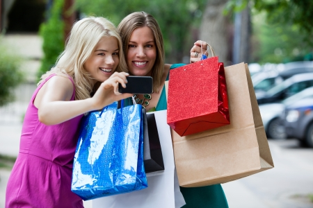sidewalk sale: Shopping Women taking self portrait with cell phone