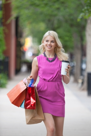 down town: Happy young woman with shopping bags and disposable coffee cup on sidewalk