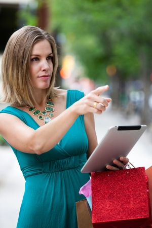 Woman using digital tablet while shopping photo