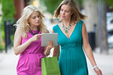 walking down: Young women with shopping bag using digital tablet