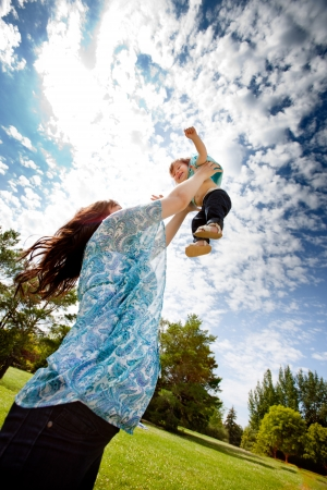 Pregnant mother in third trimester playing with her daughter in a park photo