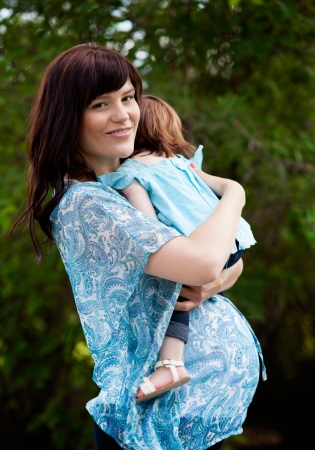 Happy pregnant mother with toddler daughter in park Stock Photo - 15222984