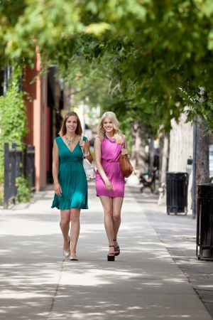 Full length portrait of young women walking on sidewalk photo