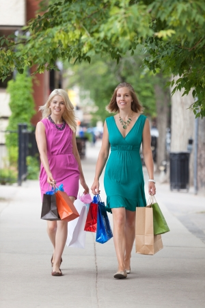 walking down: Full length of young female friends with shopping bags walking on sidewalk Stock Photo