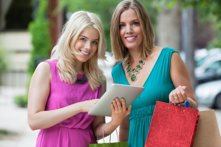 Portrait of happy young women with shopping bags using digital tablet photo