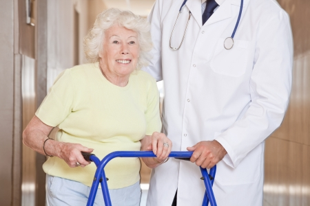 Portrait of elderly woman and doctor with zimmerframe  photo