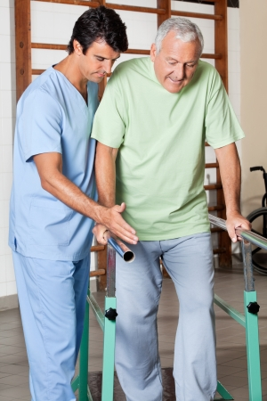 rehab: Physical therapist assisting senior man to walk with the support of bars at hospital gym