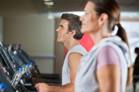 Side view of happy young man and woman running on treadmill in health club photo