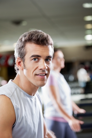 Portrait of young man on treadmill in health club photo