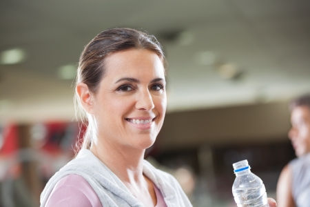 Portrait of happy mature woman holding bottle of water at health club photo