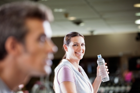 Portrait of mature woman holding bottle of water at health club photo