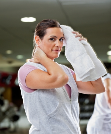 wipe: Portrait of mature woman wiping sweat with towel at health club