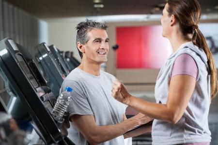 edad media: Instructor masculino feliz con el cliente de la mujer en el centro de salud