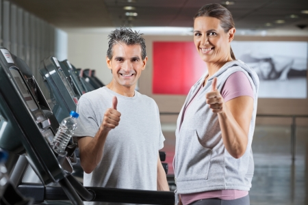 Happy mature instructor and female client showing thumbs up sign in health club - shallow depth of field, focus on trainer photo