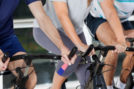 Mid section of men and woman on exercise bikes in health club photo