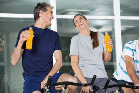 Man and woman holding juice bottles while laughing in health club photo