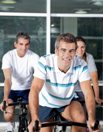 Portrait of happy people on spinning bike in health club photo