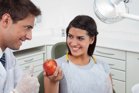 Happy male dentist showing thumbs up sign to a female patient holding an apple in clinic photo