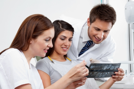 Female nurse and dentist explaining X-ray report to patient with doctor in the background photo