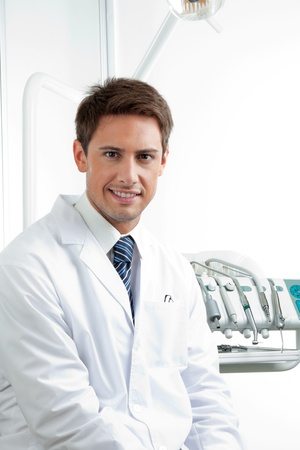 Portrait of happy male dentist sitting in clinic