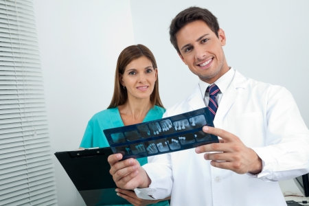 xray: Portrait of happy dentist with dental nurse analyzing X-ray report in clinic