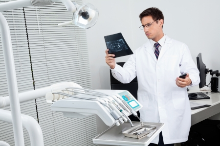 Male dentist analyzing patient s X-ray report in examination room Stock Photo - 15314700