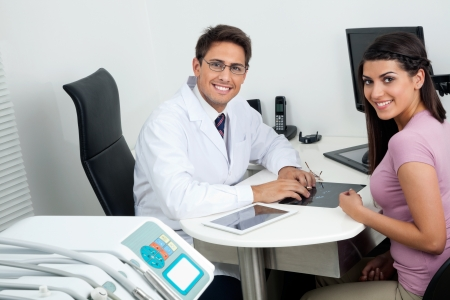 Portrait of happy young dentist and female patient sitting at office desk photo