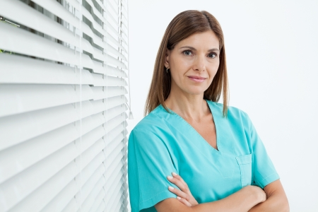 Portrait of confident female dentist standing with arms crossed in clinic Stock Photo - 15314699