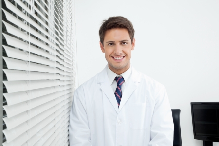 Portrait of happy young male dentist standing in clinic photo