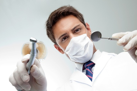 Portrait of young male dentist wearing surgical mask while holding angled mirror and drill Stock Photo - 15314672