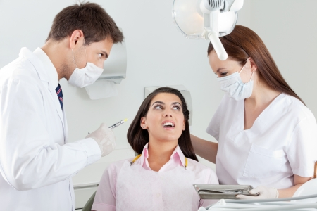 Young male dentist looking at nurse comforting patient in clinic photo
