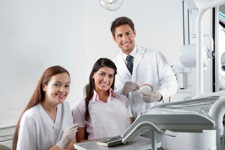 Portrait of happy young dentist and nurse with patient in clinic photo