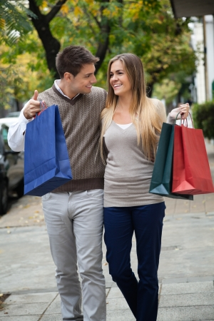 Happy young couple looking at each other while walking on pavement photo
