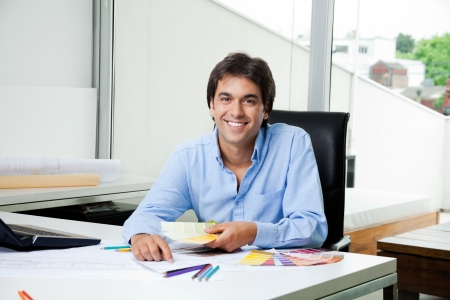 asian architect: Portrait of male interior designer working at office with color swatches