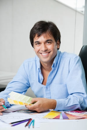 Portrait of young male interior designer smiling while holding color swatches photo