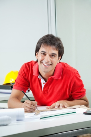 Portrait of young male architect drafting blueprint while sitting at desk Stock Photo - 15314732