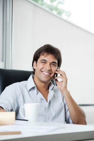 Portrait of happy male architect attending a phone call photo