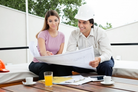 Young male architect having a discussion about house plans with female photo