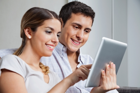 adult magazines: Beautiful young woman showing something to boyfriend on tablet PC Stock Photo