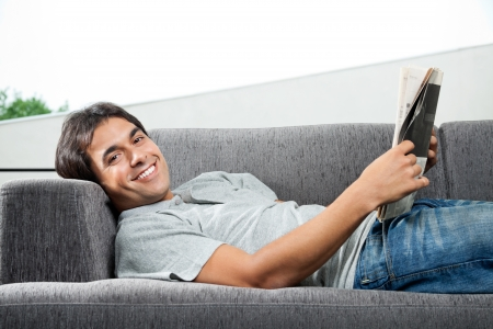 Portrait of young man in casual wear lying on sofa with a magazine photo