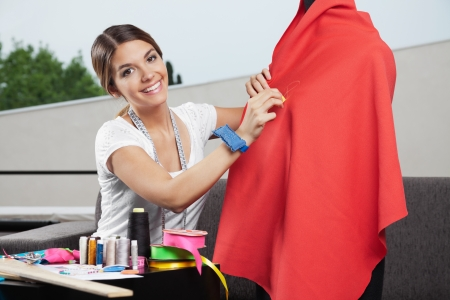 seamstress: Portrait of beautiful female fashion designer working on  red fabric with dressmaking accessories on table