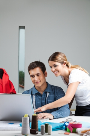 Young fashion designers working on laptop together photo