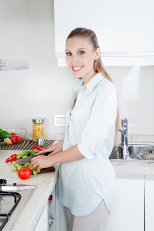 knife tomato: Blond female woman cutting vegetables in kitchen