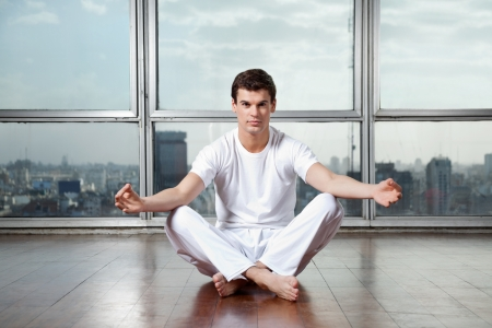 Full length portrait of a young man meditating in lotus position at gym photo