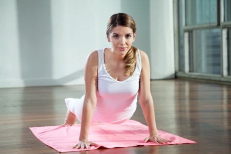 Portrait of a beautiful young woman practicing yoga on mat at gym photo