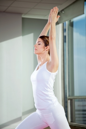 Side view of a young woman performing Crescent Moon pose at gym photo