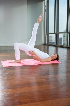 Flexible young woman practicing yoga exercise called Shoulder Stand on mat photo